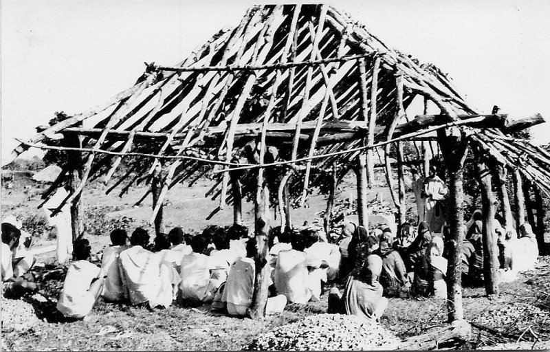 Villagers gathered in a typical 'prayer hut' which is still under construction.